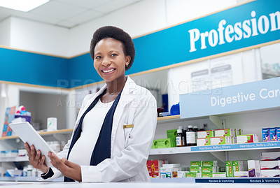 Buy stock photo Portrait of a cheerful young pharmacist working on a digital tablet inside of a pharmacy during the day