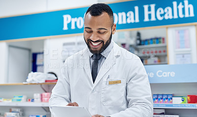 Buy stock photo Cropped shot of a cheerful young pharmacist working on a digital tablet inside of a pharmacy during the day