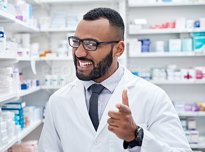 Buy stock photo Portrait of a confident young pharmacist working by himself inside of a pharmacy during the day