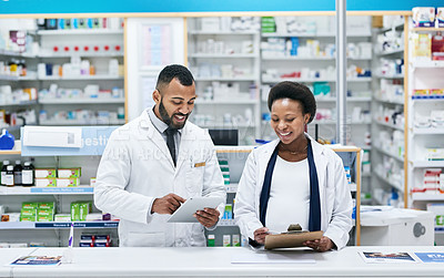 Buy stock photo Shot of two pharmacists working behind the counter in a chemist