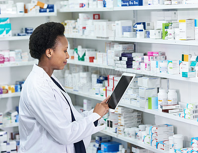 Buy stock photo Shot of a young pharmacist working on a digital tablet while checking stock in a chemist