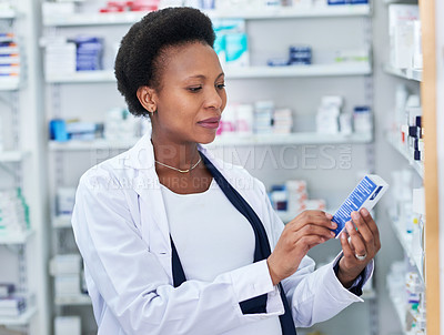 Buy stock photo Shot of a young pharmacist holding a box of medication while working in a chemist