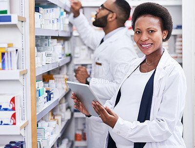 Buy stock photo Portrait of a pharmacist using a digital tablet while working with her colleague in a chemist