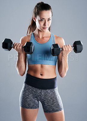 Buy stock photo Studio shot of an attractive young woman lifting weights while standing against a grey background