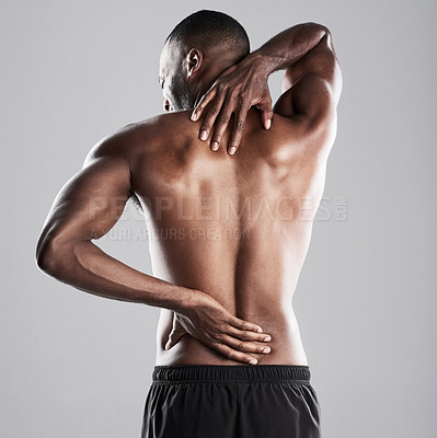 Buy stock photo Studio shot of a muscular young man showing his back to the camera while standing against a grey background