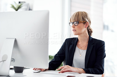Buy stock photo Shot of an attractive young businesswoman working on a computer in a modern office