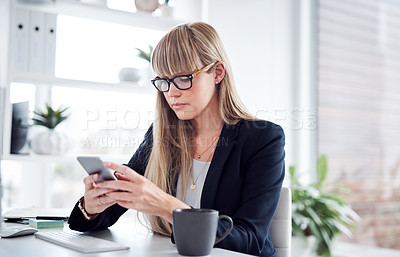 Buy stock photo Shot of an attractive young businesswoman using a cellphone at her office desk at work