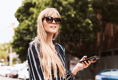 Buy stock photo Shot of a beautiful and stylish young woman using a smartphone in the city
