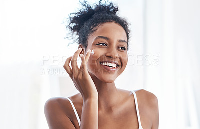 Buy stock photo Shot of a beautiful young woman applying moisturiser to her face in the bathroom at home