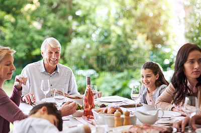 Buy stock photo Cropped shot of an affectionate family dining around the table for lunch outdoors