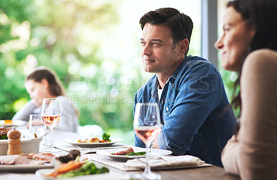 Buy stock photo Cropped shot of a young man looking attentive while dining on the table with his family