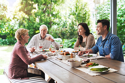 Buy stock photo Cropped shot of an affectionate young couple enjoying lunch with their aged parents outdoors