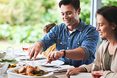 Buy stock photo Cropped shot of ann attractive young man cutting the chicken during lunch with his family outdoors