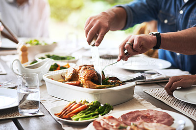 Buy stock photo Cropped shot of an unrecognizable man cutting the chicken during lunch with his family outdoors