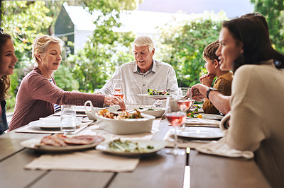 Buy stock photo Cropped shot of an affectionate aged man enjoying lunch with his family outdoors