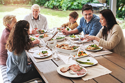 Buy stock photo High angle shot of a cheerful family enjoying lunch around a table outdoors