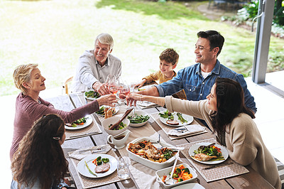 Buy stock photo High angle shot of a cheerful family making a toast while having lunch outdoors