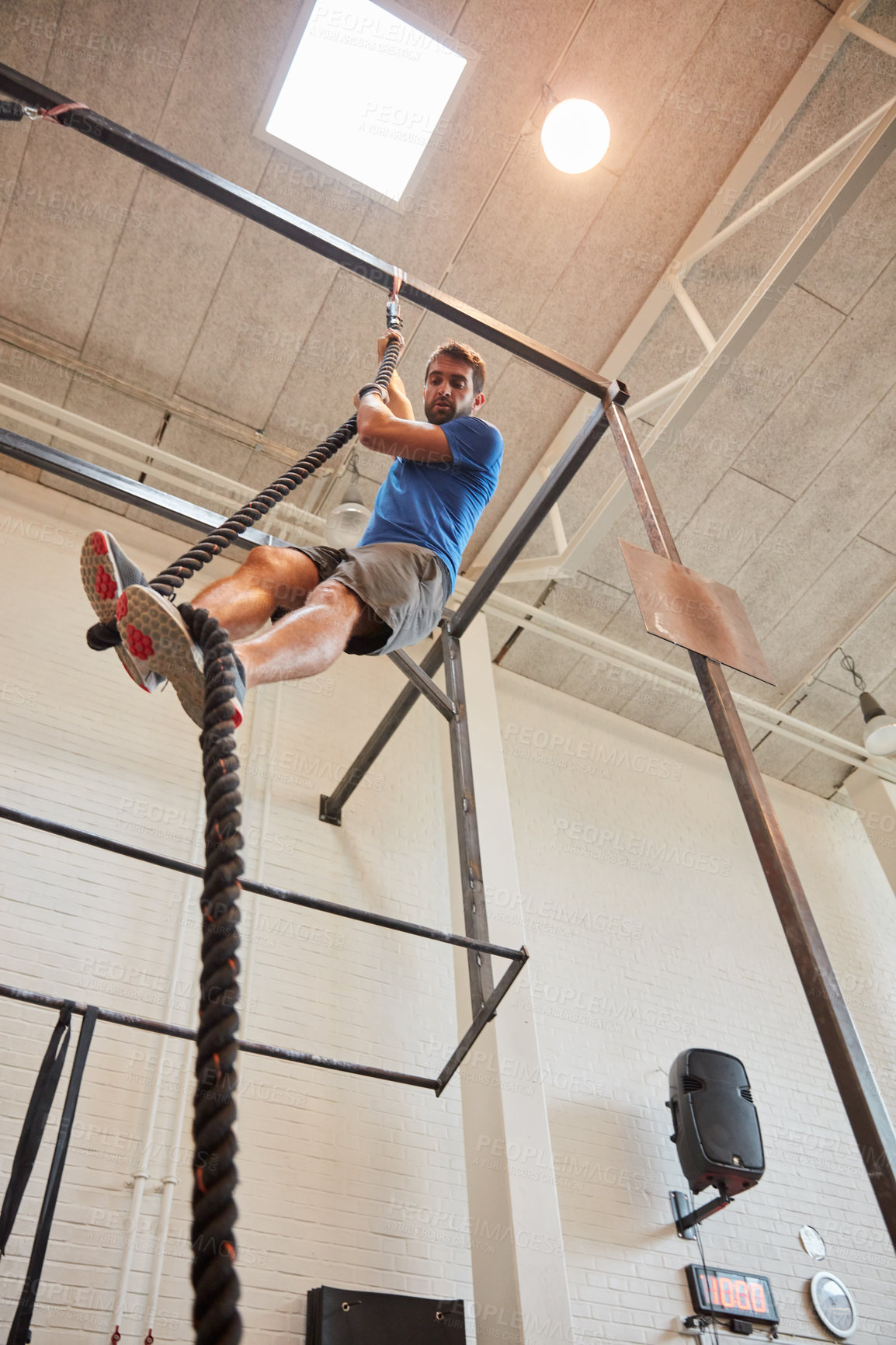 Buy stock photo Low angle shot of a handsome young man rope climbing while working out in the gym