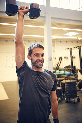 Buy stock photo Cropped shot of a handsome young man working out with a dumbbell in the gym