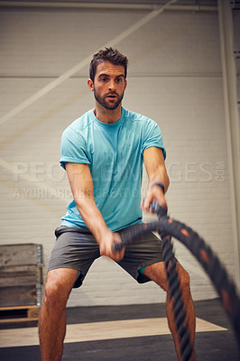 Buy stock photo Cropped shot of a handsome young man working out with battle ropes in the gym