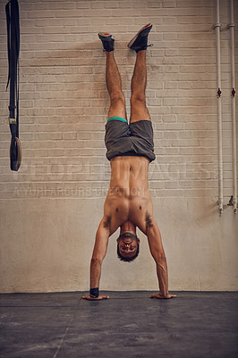 Buy stock photo Full length portrait of a handsome young man doing handstands while working out in the gym