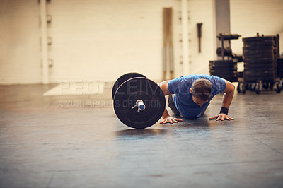 Buy stock photo Full length shot of a handsome young man doing pushups while working out in the gym