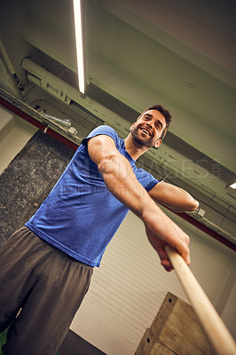 Buy stock photo Low angle shot of a handsome young man working out with a stick in the gym