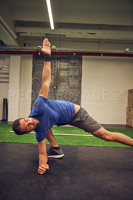 Buy stock photo Cropped shot of a handsome young man stretching while working out in the gym