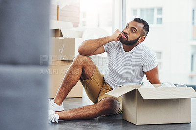 Buy stock photo Shot of a young man looking unhappy while moving house