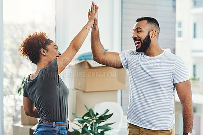 Buy stock photo Shot of a young couple giving each other a high five while moving house