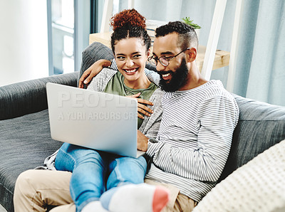 Buy stock photo Shot of a couple using a laptop while relaxing on the sofa at home