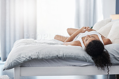 Buy stock photo Shot of an unrecognizable young woman lying on her bed facing up