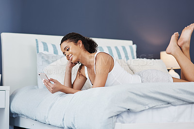 Buy stock photo Shot of an attractive young woman using her smartphone while relaxing on her bed at home
