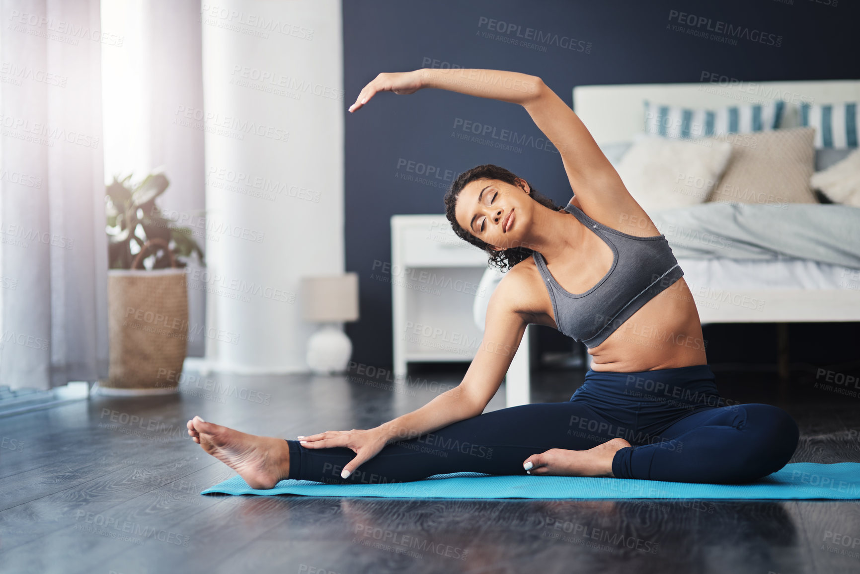 Buy stock photo Shot of an attractive young woman practicing yoga in her bedroom in the morning