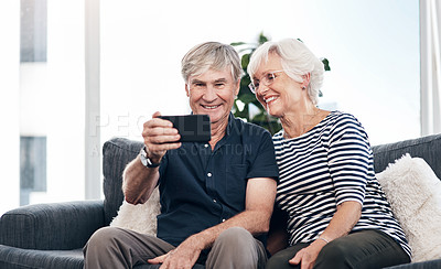 Buy stock photo Shot of a happy senior couple taking selfies with a smartphone while relaxing together on the sofa at home