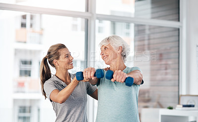 Buy stock photo Shot of a young physiotherapist assisting a senior patient with strengthening exercises