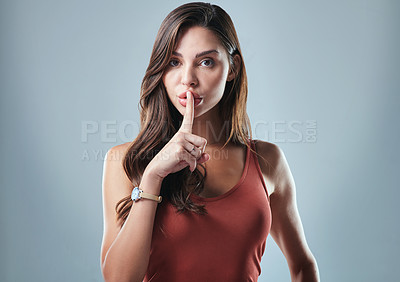 Buy stock photo Studio shot of a young woman posing with her finger on her lips