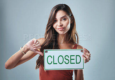 Buy stock photo Studio shot of a young woman holding a closed sign against a grey background