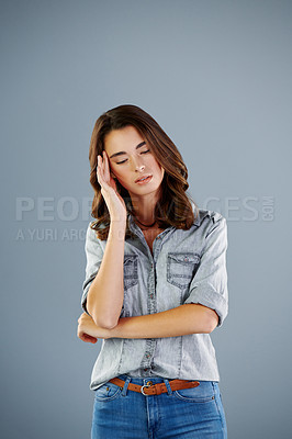 Buy stock photo Studio shot of an attractive young woman suffering with a headache against a grey background