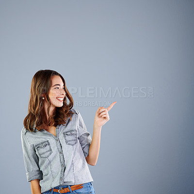 Buy stock photo Studio shot of an attractive young woman pointing towards copyspace against a grey background