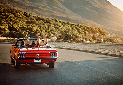 Buy stock photo Shot of happy young friends enjoying a summer's road trip together