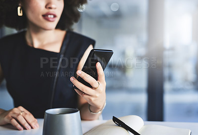 Buy stock photo Shot of an unrecognizablel businesswoman using a cellphone while working in her office