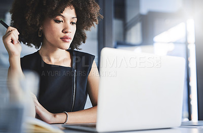 Buy stock photo Shot of a beautiful young businesswoman working on a laptop in her office