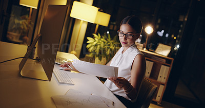 Buy stock photo Shot of a beautiful young businesswoman sorting out paperwork while working late in her office