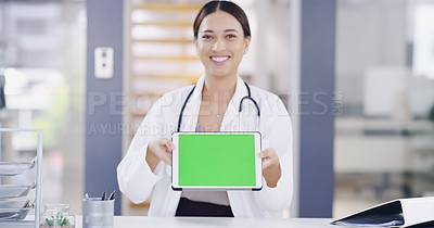 Buy stock photo Portrait of a young doctor holding a digital tablet with a green screen in a modern hospital