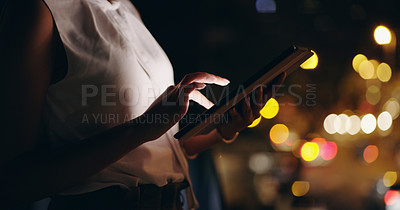 Buy stock photo Shot of an unrecognizable businesswoman using a digital tablet while out in the city at night