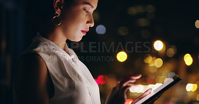 Buy stock photo Shot of a beautiful young businesswoman using a digital tablet while out in the city at night