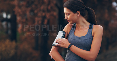 Buy stock photo Cropped shot of a sporty young woman using her device in her armband while out for a run