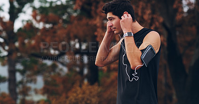 Buy stock photo Shot of a young man putting in his earphones before his run