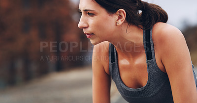 Buy stock photo Cropped shot of a sporty young woman taking a break while out running